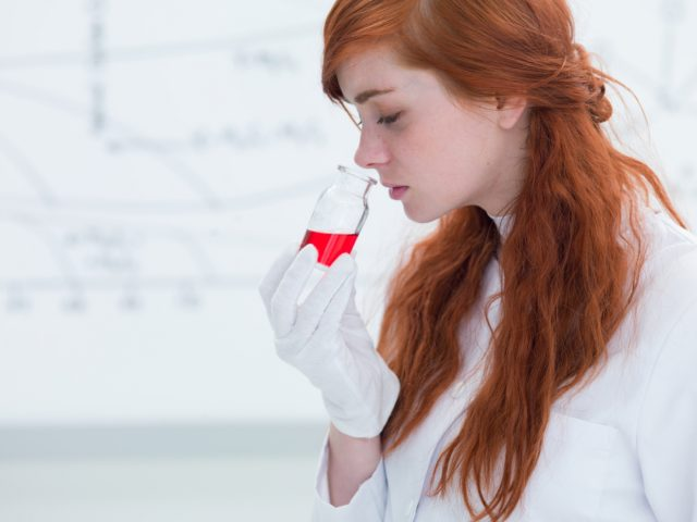 close-up of a pretty student in a chemistry lab smelling colorful substances and a white-board on the background; Shutterstock ID 135110156; PO: 20161020_FD; Job: Fleetdriver; Client: Volkswagen; Other: Eva Syed