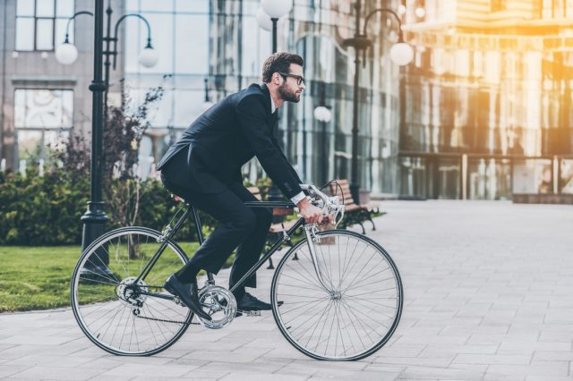 On the way to work. Side view of young businessman looking forward while riding on his bicycle; Shutterstock ID 428217643; PO: FD-20161025; Job: Fleetdriver; Client: Volkswagen AG; Other: Eva Syed